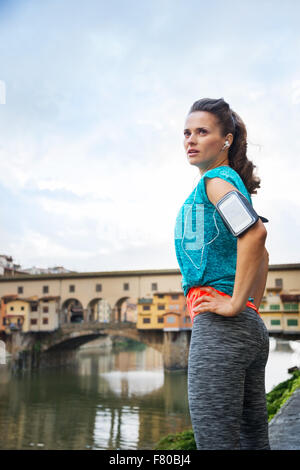 Relaxed young woman in fitness outfit standing next to Arno river in Florence, Italy - Stock Photo