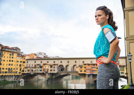 Fitness woman in sportswear standing next Ponte Vecchio bridge and looking at distance before outdoor jogging in - Stock Photo