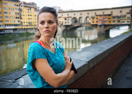 Young сoncentrated woman in sportswear is staying next to Ponte Vecchio bridge with mp3 player and getting ready - Stock Photo