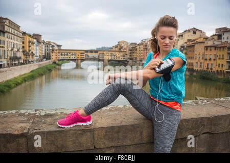 Sporty young woman sitting in front of Ponte Vecchio and listening music on mp3 player, seeing which song is going - Stock Photo