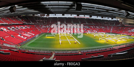 Manchester United pitch with solar lamps on grass turf in winter - Stock Photo