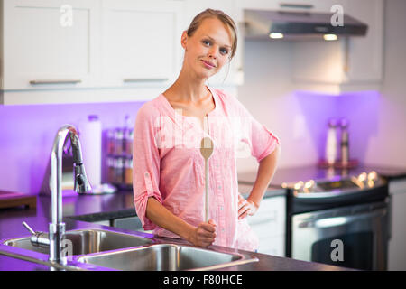 Pretty, young woman posing in her modern kitchen, holding a wooden spoon, ready to cook something delicious (shallow - Stock Photo