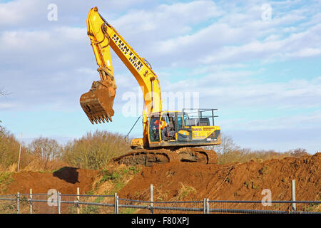 A lone digger on the top of a freshly dug earth mound, bucket and driver at the ready. - Stock Photo