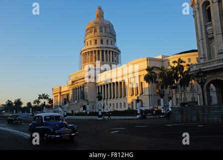 Havana, Cuba. 29th Oct, 2015. A classic car drives along the Paseo de Mart' as the rising sun lights up El Capitolio, - Stock Photo