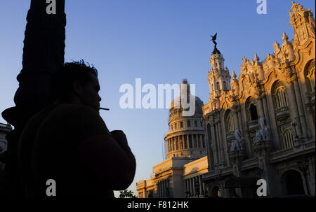 Hanava, Cuba. 29th Oct, 2015. A man smokes as the rising sun lights up El Capitolio, or National Capitol Building - Stock Photo