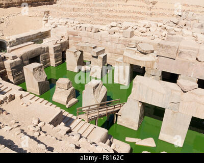 The Osireion at the Temple of Seti I at Abydos, with bright green algae in water, Nile Valley, Egypt, Africa - Stock Photo