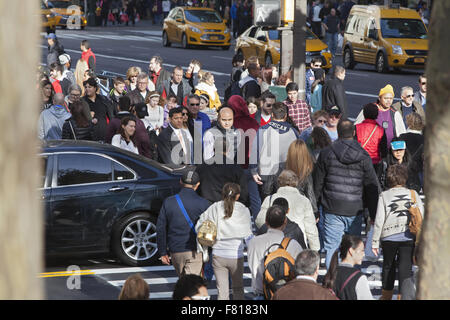 Crowds of tourists and shoppers cross 42nd St. at 5th Ave. on Black Friday the official start of the holiday shopping - Stock Photo