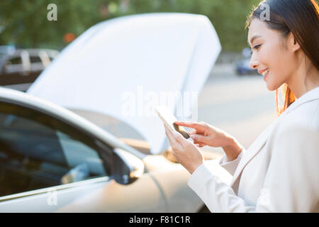 Female driver messaging on mobile phone next to broken down car - Stock Photo
