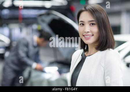Young woman in repair shop with her car - Stock Photo