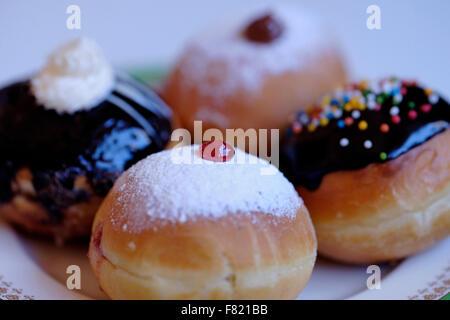 Elegantly traditional Sufganiyot deep fried round doughnut eaten during Hanukkah Jewish feast - Stock Photo