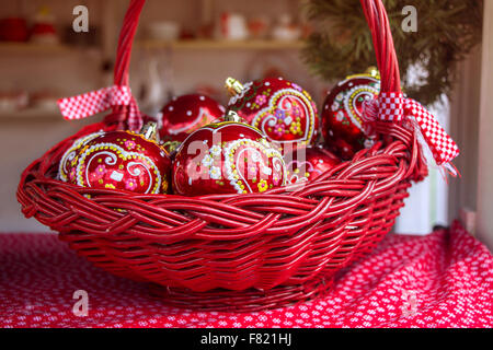 Red Christmas balls in basket, decorated with gingerbread heart, a traditional Croatian  decorations