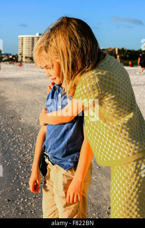 Young pre-teen sister giving her younger brother a hug on Siesta Key beach in Florida - Stock Photo