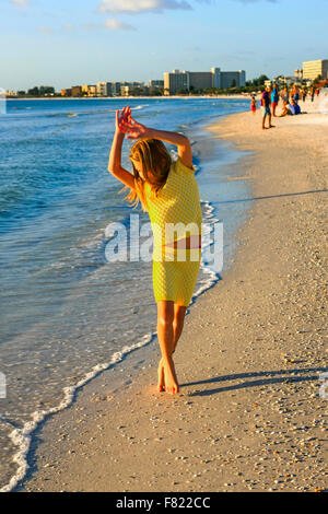Young pre-teen girl dancing at sunset on the beach at Siesta Key Florida - Stock Photo
