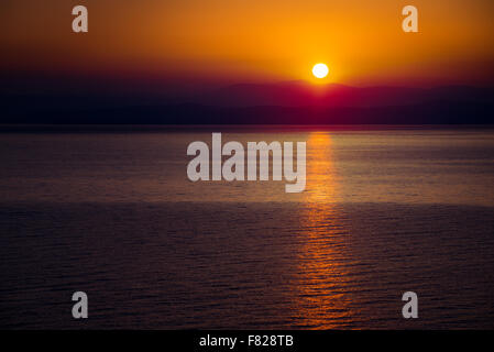 The Rising Sun Over the Sea with Beautiful Vibrant Red Glow and Reflection on the Water. Mountains in Background. - Stock Photo