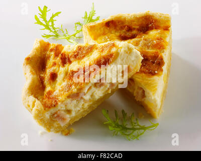 Slices of quiche Loraine on a white background - Stock Photo