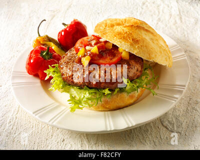 Close of a beef burger, hambuger in a white crusty roll with tomato relish and peppersand lettuce - Stock Photo