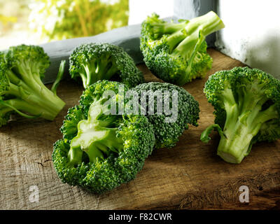 Close up of fresh whole and cut uncooked florets of brocoli (  Brassica oleracea) - Stock Photo