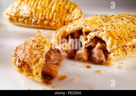 Traditional British beef pastry pie served on a white plate on a table in a  traditional kitchen setting ready to - Stock Photo