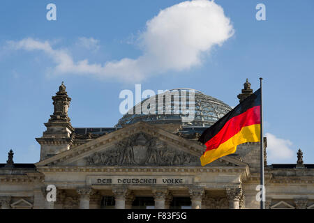 The German flag flying in front of the Reichstag building in Berlin, Germany. German parliament with glass dome - Stock Photo