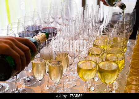 waiters poured into glasses of wine and champagne - Stock Photo