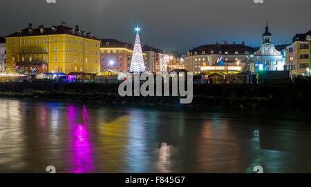 Night shot of Innsbruck Christmas Market in Marktplatz, viewed by Inn river bank - Stock Photo