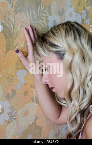 Sad young woman leaning against the wall - Stock Photo