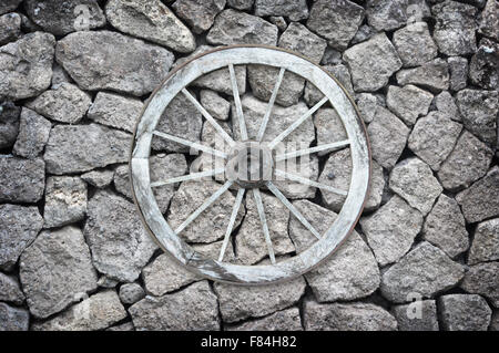 Beautiful old-fashioned wooden wagon wheel set on a stone wall. - Stock Photo