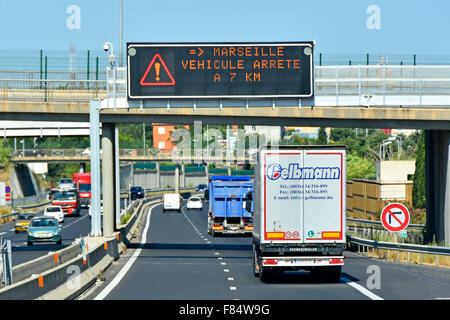French autoroute lorry traffic below gantry mounted electronic information sign in Provence France - Stock Photo