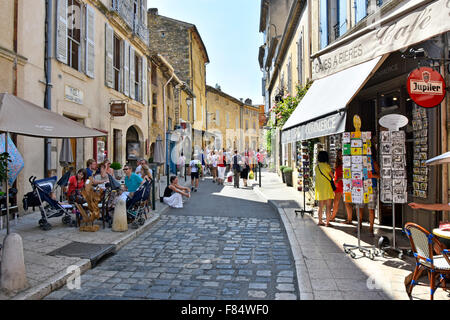 Lourmarin village in the Luberon area of Provence tourists relaxing in the shade at outdoor café tables in narrow - Stock Photo