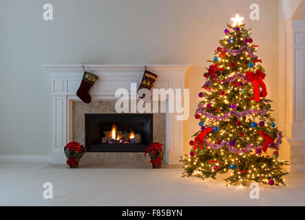 Bright Christmas tree and glowing fireplace in living room. - Stock Photo