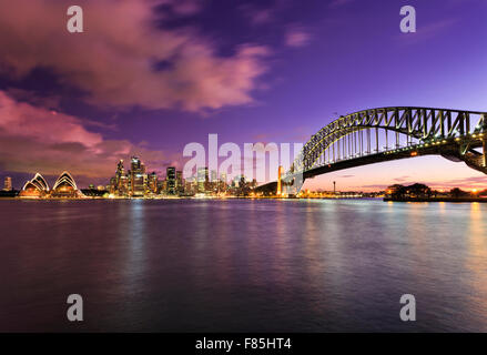 main Sydney landmarks at sunset across harbour with blurred clouds and water reflecting bright lights of colourful - Stock Photo