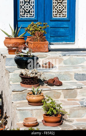 Santorini. Close up of stone steps leading to blue front double doors with small various shaped clay round plant - Stock Photo