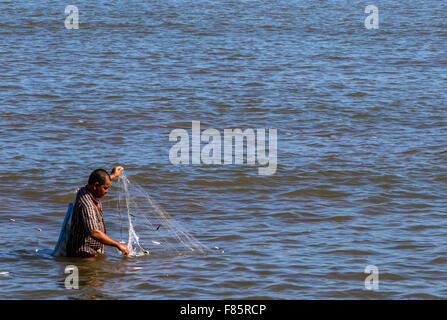 Man fishing in Likas bay in South China Sea off Kota Kinabalu Sabah East Malaysia on Island of Borneo - Stock Photo