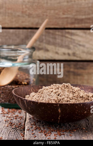 flax flour in a bowl, flax seeds in a glass jar on a wooden background - Stock Photo