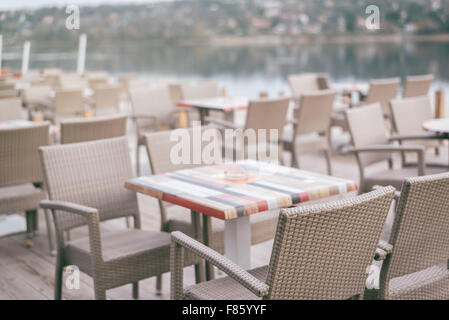 Empty cafe terrace on late autumn afternoon with no guests, chairs and tables retro toned, selective focus - Stock Photo