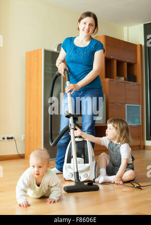 Happy mother wth two children cleans living room with vacuum cleaner - Stock Photo