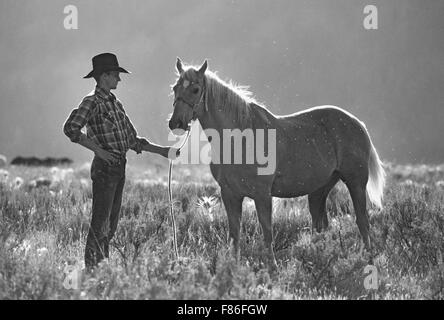 A cowboy stands with his horse in a mountain meadow on a cattle ranch in the American West - Stock Photo
