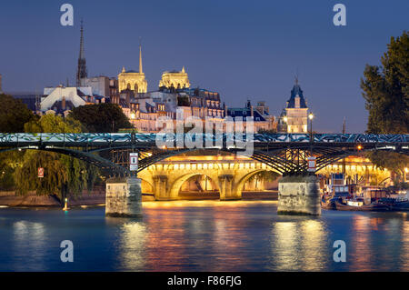 Pont des Arts, Pont Neuf, Notre Dame de Paris Cathedral towers and Seine River. Illuminated evening view. Ile de - Stock Photo