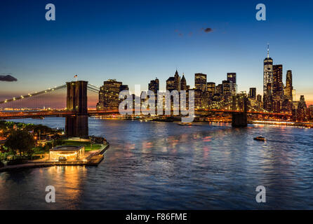 Brooklyn Bridge and illuminated Lower Manhattan at twilight. Financial District skyscrapers reflect in the East River, New York.