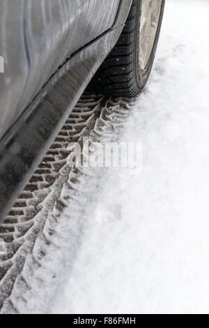 Parked car creates snow tire prints in the wintery chill of the first snow storm to hit vehicle users in the icy - Stock Photo