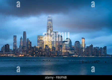 Lower Manhattan and Financial District illuminated skyscrapers with storm clouds, New York City. World Trade Center - Stock Photo