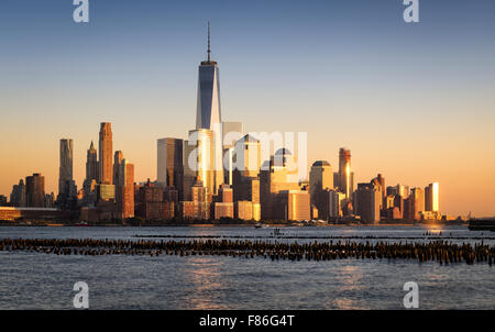 Lower Manhattan Financial District skyscrapers at sunset across Hudson River with World Trade Center. New York City - Stock Photo