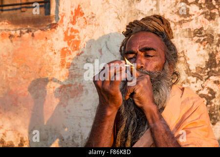 A Sadhu smoking ganja, holy man, Galtaji, Khania-Balaji, Jaipur, Rajasthan, India - Stock Photo
