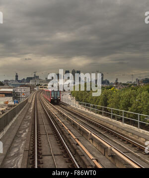 Docklands Light Railway (DLR) and the towers of Canary Wharf, London, on a cloudy day - Stock Photo