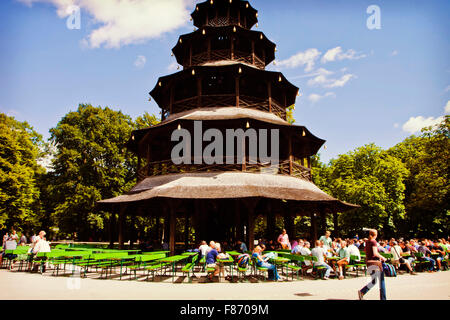 MUNICH, GERMANY - People seat in the sun at Chinese tower beer garden at Englisher Garten in Munich - Stock Photo