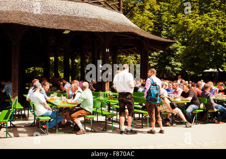 MUNICH, GERMANY -  People sitting in the sun on the benches of Chinese tower beer garden at Englisher Garten in - Stock Photo