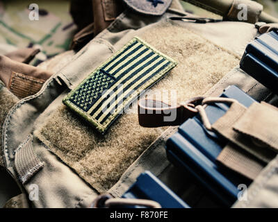 Green US flag patch on the tactical bulletproof vest with M4 magazines, selective focus - Stock Photo