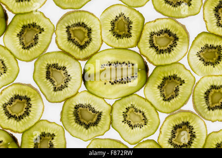 exotic kiwi fruit backlit in studio cut cross and longitudinal sections showing internal seed distribution around - Stock Photo