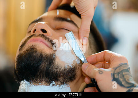 Professional barber shaving the beard of his client - Stock Photo