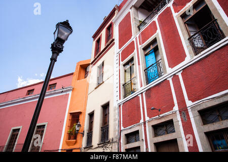 Blue door, red building, along the colorful streets of Guanajuato, Mexico. - Stock Photo